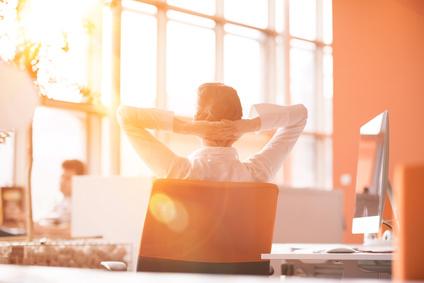 Frau blickt entspannt am Schreibtisch zur Sonne